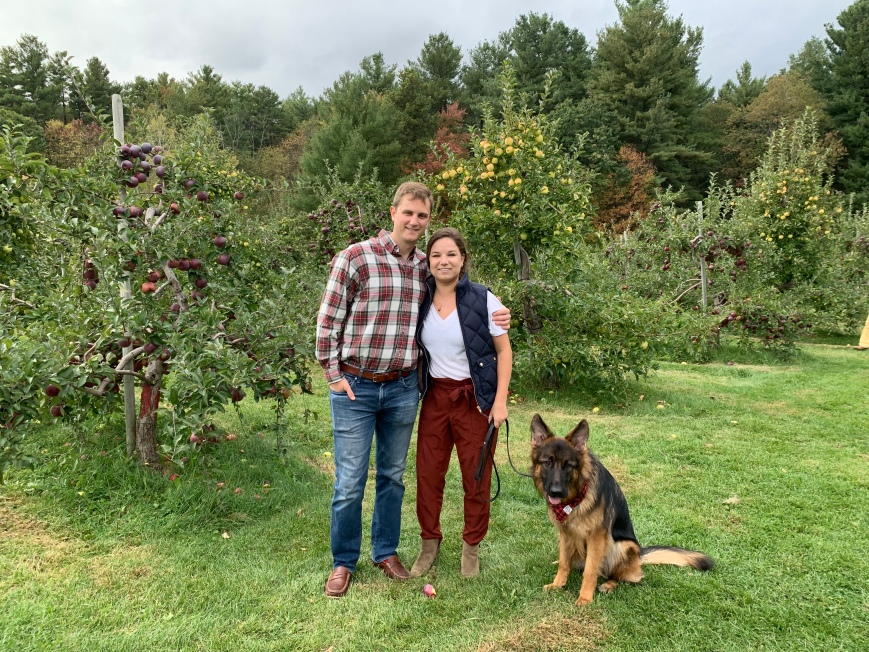 family with dog in an apple orchard in New England