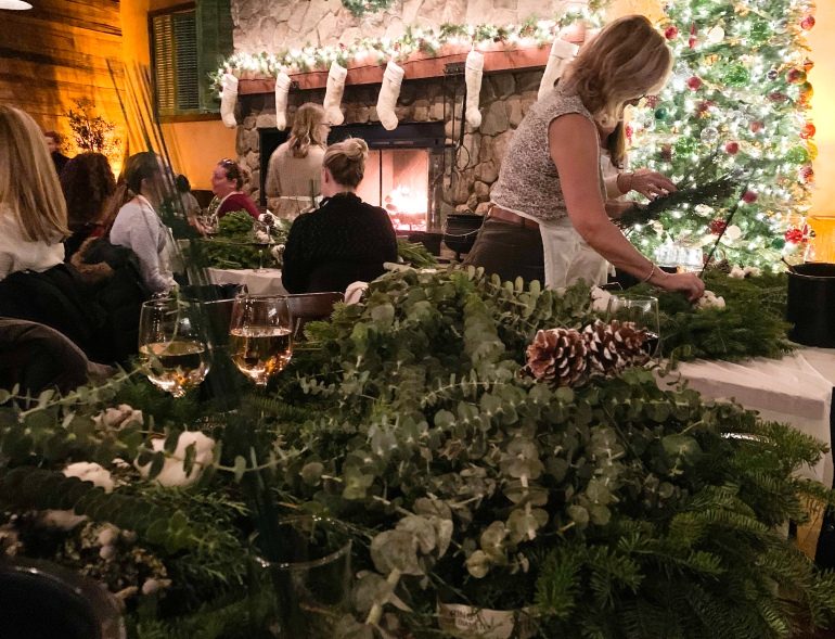 woman making a holiday wreath at Capo in Boston