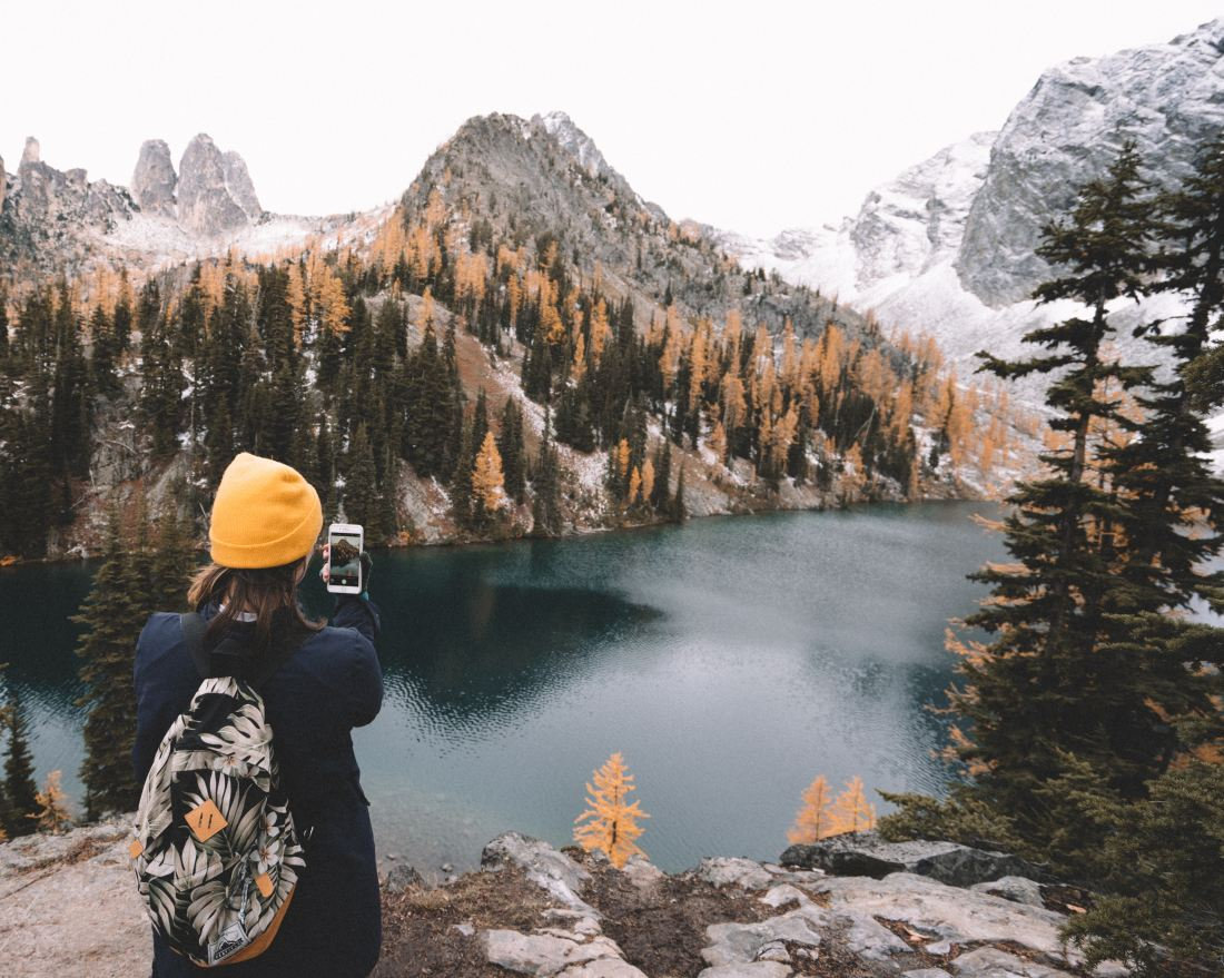 a girl taking a picture of a lake and mountains